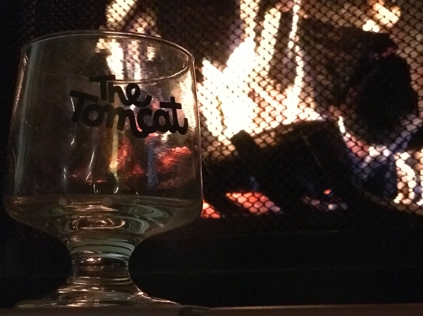 Small stemmed glass on the left foreground with a roaring fire behind